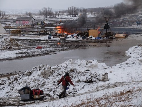 Image Credit: Dan Gunderson / MPR News - Campsite burns as protesters leave the Oceti Sakowin camp near Cannon Ball, N.D. Feb. 22, 2017